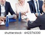 woman handing in her resume to... | Shutterstock . vector #642376330