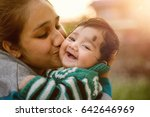 Young Indian Mother Kissing He...