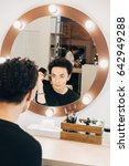 Small photo of Attractive woman primp at the mirror with lamps in the beauty studio. A happy satisfied customer of make-up and hairstyle service.