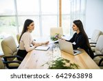 Small photo of Two business woman sitting at desk: customer and adviser talking together.