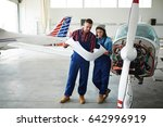 Stock photo two modern aircraft engineers man and woman reading construction plans standing by disassembled 642996919
