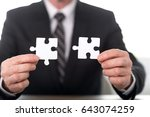 hands joining two puzzle pieces ... | Shutterstock . vector #643074259