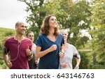 Mature woman running with group ...