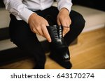 man puts on black leather shoe | Shutterstock . vector #643170274