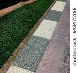 Small photo of Different colours of pea gravels or chips binded together to create alternate patterns to decorate and brighten up border along concrete footpath and grass edge