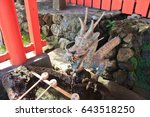Stock photo pure spring water spouts from the mouth of a metal dragon at the entrance to a shinto shrine in 643518250