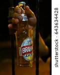 Small photo of SANTO DOMINGO, DOMINICAN REPUBLIC - SEPTEMBER 21, 2012: Brahma Light - popular cold drink on Caribbean. Man holds icie bottle of beer behind window cage.