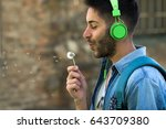 handsome man blowing dandelion. | Shutterstock . vector #643709380