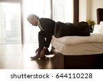 man with luggage puts on shoes... | Shutterstock . vector #644110228