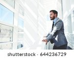 Portrait of a young successful businessman thinking about something while looking in big office building, confident serious men entrepreneur dressed in formal wear enjoying calm after hard work day  - stock photo