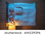 the happy couple lie on the bed.... | Shutterstock . vector #644239396