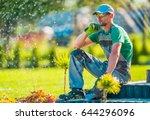 Professional Caucasian Garden Designer in His 30s Taking Break To Rethink New Landscaping Ideas. Gardening Concept. - stock photo