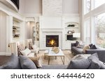 Beautiful living room interior with hardwood floors and fireplace in new luxury home. Large bank of windows hints at exterior view - stock photo