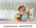 Stock photo little baby girl sit on the bed with labrador puppy 644520700