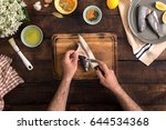 man cooking fish on a rustic... | Shutterstock . vector #644534368