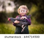 Stock photo caucasian baby boy posing with hen happy child on farm 644714500