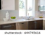 Stock photo luxury kitchen with natural backsplash white quartz natural brown wood cabinets and lots of light 644745616