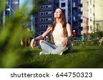 Stock photo young woman sitting in lotus position on the lawn in the courtyard of a residential block 644750323