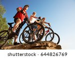 Small photo of Three bicyclists on the brink of a rock look afar from rock breakage at beautiful lake