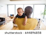 Small photo of Young afro-american father holding his baby son in the arms