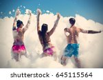 two women and a man at a foam... | Shutterstock . vector #645115564