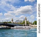 Small photo of Paris, France, passenger ship passes under Alexander III bridge on Seine river on a bright day in Spring. Panoramic image, square composition.