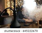 man smoking pipe of hookah in a ... | Shutterstock . vector #645222670