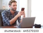 Stock photo young man smiling slightly as he flirts via text message on his phone while seated at his desk 645270103
