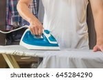 Small photo of Man ironing shirt on ironing board with steaming blue iron.