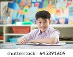 happy asian child reading book... | Shutterstock . vector #645391609