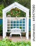 Small photo of Mr and Mrs die cut wedding garland on string under white arch in garden with heart shaped flower wreath and vintage bench in garden