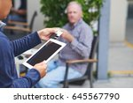 Small photo of Waiter using credit card reading device to accept payment