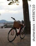 Small photo of The bicycle stands near the tree against the sky. Against the background of mountains