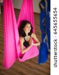 Small photo of Young female person in pink hammock doing aero yoga