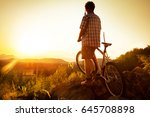 mountain cyclist look at sunset | Shutterstock . vector #645708898