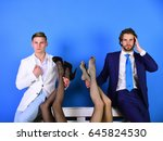 Small photo of fashion and business, handsome men in suit holding female legs in fashionable shoes and tights, luxury and patriarchy