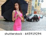 Stock photo rainy day young woman in pink dress with umbrella standing on the street 645919294