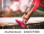 Small photo of Runner woman getting ready to run tying running shoes laces. Healthy lifestyle jogging motivation closeup of feet or footwear.