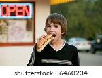 boy eating a footlong hot dog | Shutterstock . vector #6460234