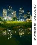 Small photo of Skyline of skyscrapers illuminated at night with Sam Houston Park illuminated at night