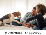 Stock photo portrait of an african american father and daughter enjoying spending time with dog in the bed 646214920