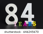 Small photo of Letters and numbers eighty-four on a black isolated background.