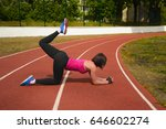 beautiful girl doing exercise. sexy girl in sportswear at the stadium.a red sports tank top and tight black leggings. the enjoyment of sports and healthy lifestyle.