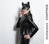 Small photo of Beautiful dominant brunette vamp goth mistress evil girl in latex dress, spiky collar and bdsm black leather fetish cat mask posing on white backgroung