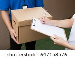 woman accepting a delivery of... | Shutterstock . vector #647158576