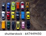 Stock photo horizontal top view assorted metal colorful toy car collection on brown wooden floor in natural 647449450