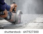 Small photo of Worker using tool to cut concrete floor with dust in background and copy space in the right