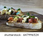 Small photo of Bruschetta with mozzarella and tomatoes, decorated with alfalfa sprout