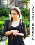 Small photo of Portrait of young woman in black chiffon dress with white dots and long braids looking at silver locket gift remembering her lover.