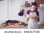 young woman reading cookbook in ... | Shutterstock . vector #648267538